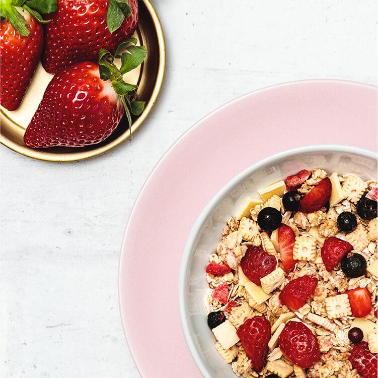Frische Erdbeeren und eine Müsli Schüssel gefüllt mit Strawberry Cheesecake Müsli
