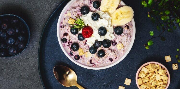 Porridge mit frischen Blaubeeren, Bananen und Schlagsahne.