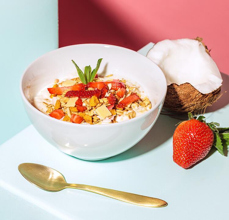 frische Erdbeeren, Kokosnüsse und Müsli in einer Schale.