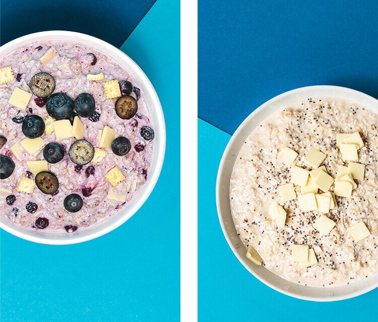 2 Schalen mit Porridge und frischen Blaubeeren und Mini-Butterkeksen und Frischkäseplättchen