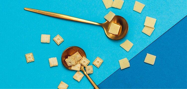 2 goldene Löffel mit den exklusiven Jubiläums-Zutaten Mini-Butterkekse und Frischkäseplättchen