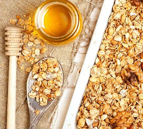 Granola wird aus Haferflocken und Bienenhonig gebacken